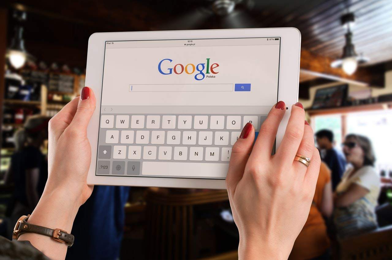 Woman in bar conducting a Google search on a tablet